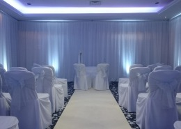 white wall drapes pipe and drape with uplighters and chair covers and aisle runner at solent hotel and spa