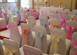 queens hotel southsea white chair cover and pastel pink yellow blue and lace sash Everything But The Dress